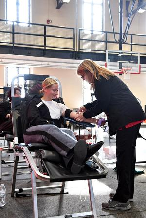 A nurse prepares Lauren Kattmann '23 for donating blood during the blood drive