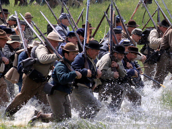 Reenactors charge across field through water