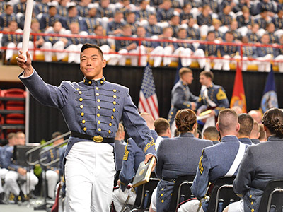A cadet waves his diploma in the air as he crosses the stage.
