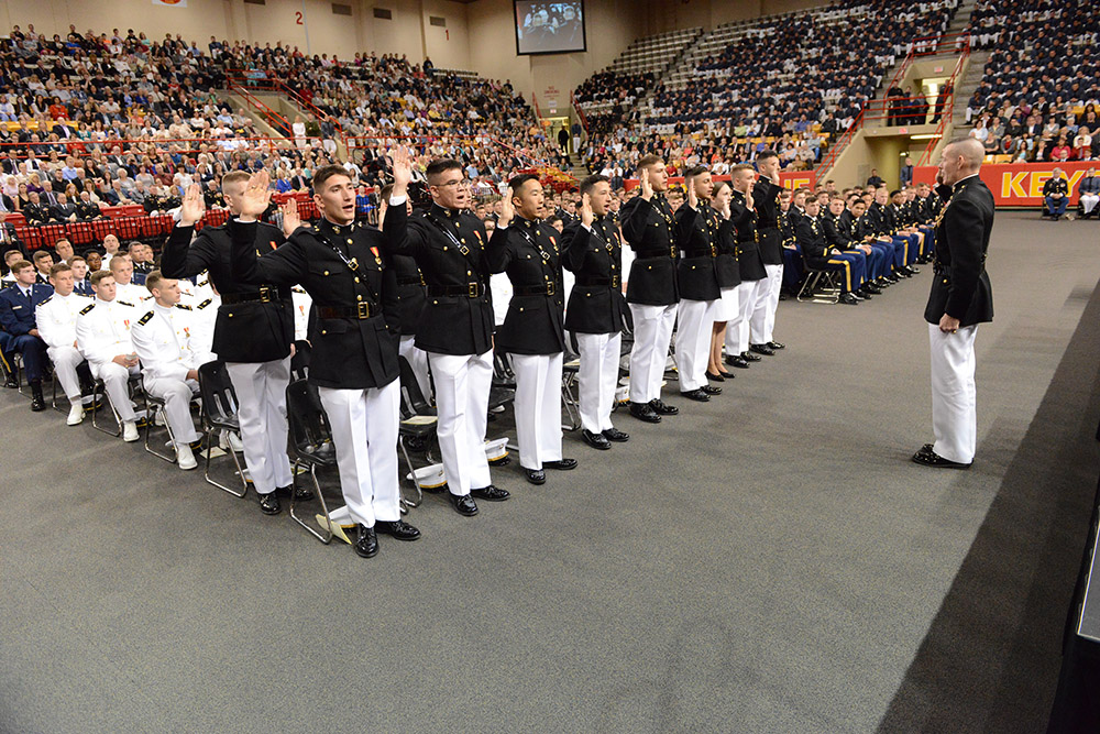 Cadets commissioning into the U.S. Marine Corps stand to take the oath.