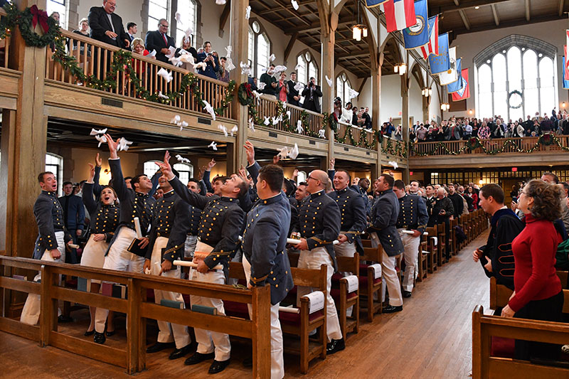 Cadets toss their gloves into the air in Jackson Memorial Hall.