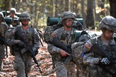 Cadets patrol through the forest during field training exercises.