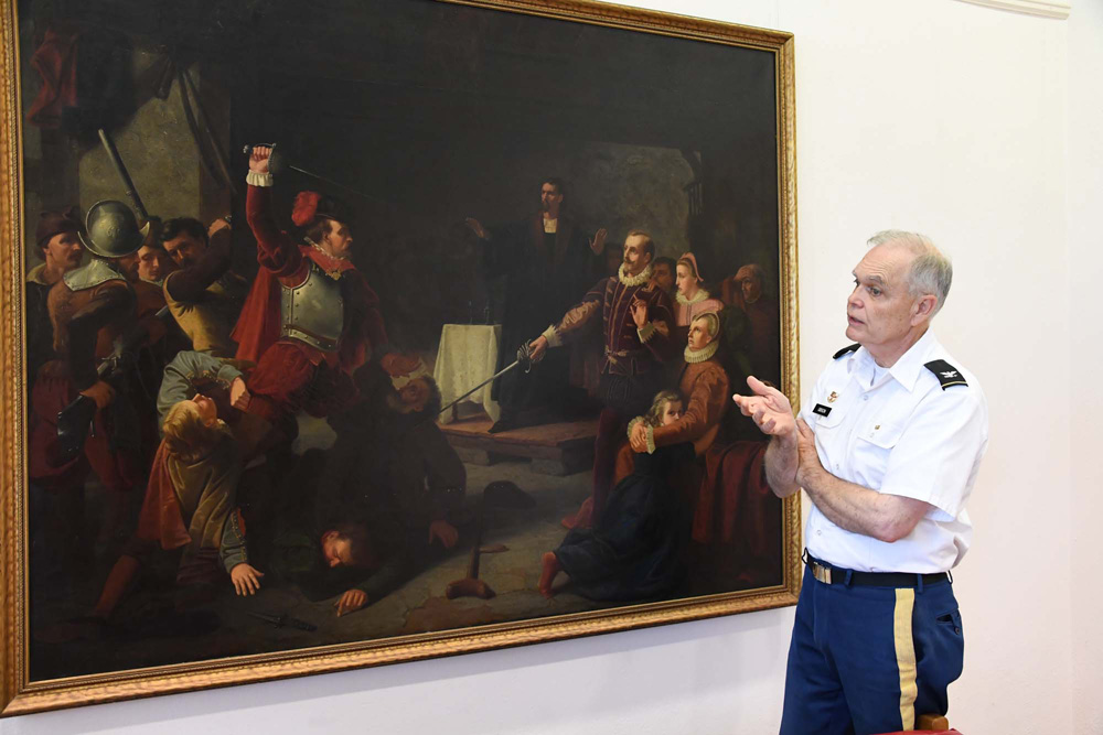 Col. Keith Gibson stands next to the painting