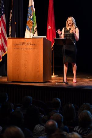 Image of Christine McKinley speaking on Gillis Theater stage