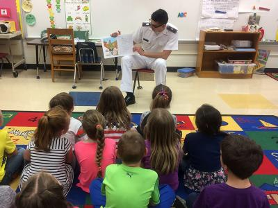 A cadet reads to elementary school students.