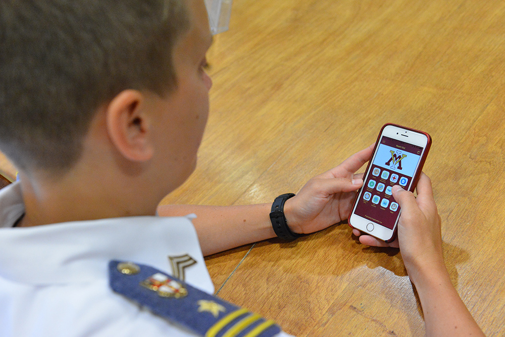 A cadet holds a cell phone displaying the Reach Out app.