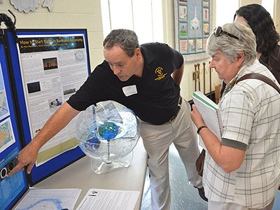 Col. Greg Topasna talks astronomy with science fair participants.