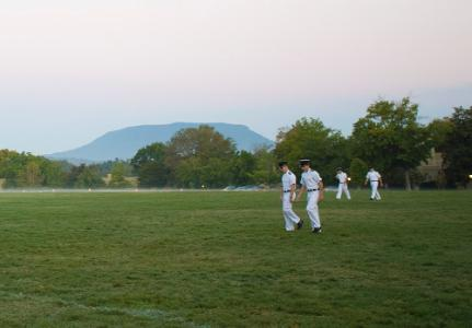 Cadets walk across the VMI Parade Ground at daybreak.