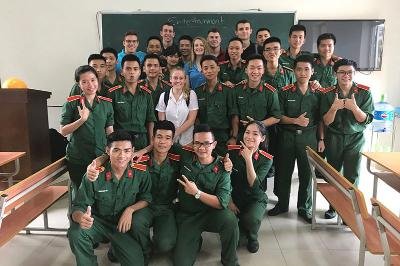 Cadet Hannah Gillan Poses with a group of students in Vietnam.