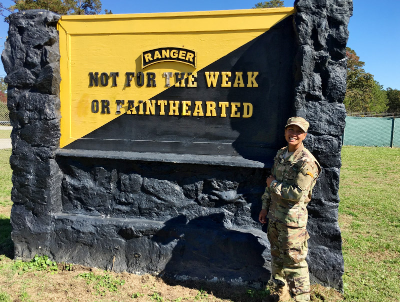 Nina Srikongyos '15 poses in front the Army Ranger school sign at Victory Pond in Fort Benning, Georgia, after her graduation in November.—Photo courtesy of Nina Srikongyos '15.