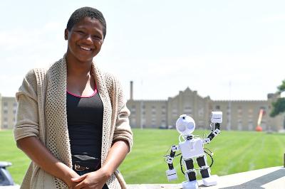Miyah Boyd pauses with her robot on the porch of Moody Hall.—VMI Photo by H. Lockwood McLaughlin.