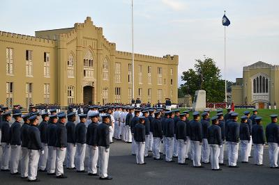 Cadets stand in front of barracks at the end of the day as the evening gun is fired.