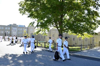Cadets in their white summer uniforms walk under a tree on their way to class.
